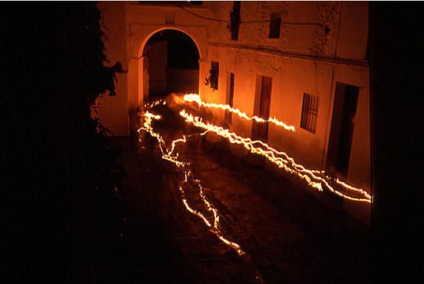 Sobre la fortaleza iluminada en la madrugada de Setenil se reflejan las sombras de los  penitentes que procesionan en El Silencio. Foto: Mario García Vargas