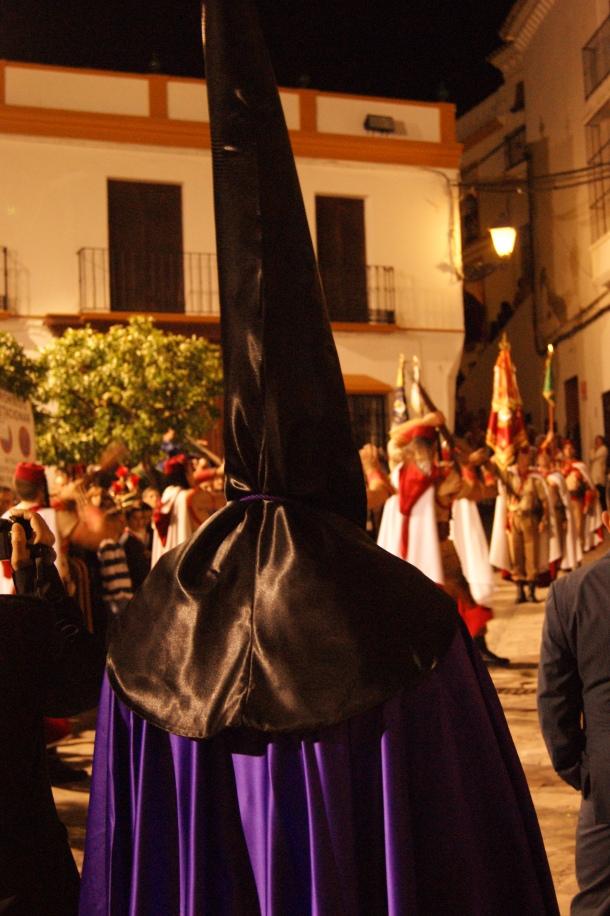La indumentaria de Los Negros consta de túnica y antifaz negro y capa y cinturón morado, aunque pueden llevar también un cinto de esparto como las zapatillas. En esta imagen, un penitente observa el desfile de Los Regulares en la Plaza. Foto: LOLI CALVENTE