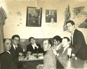 """BARES EN LA PLAZA. El bar y, más en concreto la Plaza, eran el lugar de encuentro. Esta imagen fue tomada en el bar de la plaza que llevaba un veinteañero Pedrín. En la imagen aparecen, de izquierda a derecha, Sebastián Guzmán (marido de Paca """"Basmales""""), Juan Luque, Juan Carrasco, Blas Camacho, Antonio Luis el del Estanco, y Francisco Cintado. De pie, en la barra, Pedrín."""