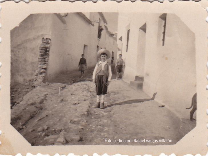 CALLES EMPEDRADAS. Bartolomé Villalón Tornay vestido de pastor, posiblemente para la misa del Gallo. Los muros de la calle Triana aún están derruidos por la riada del 49.