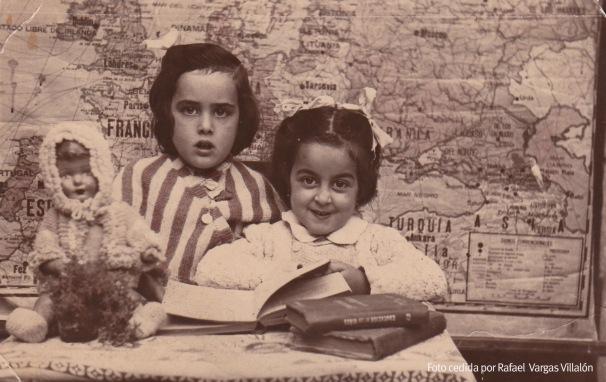 """COLEGIO. Preciosa fotografía de María Teresa y Josefa (Filo) Villalón Tornay en la escuela, con su muñeca y el mapa de una Europa que le había dado la espalda a Franco. Eran los tiempos de la Enciclopedia Álvarez que retrató con ternura y humor el libro """"El Florido pensil"""" de Andrés Sopeña. Los niños y las niñas estaban separados en dos """"aulas"""" que había en la Villa y encima del Callejón. Una de las maestras de entonces eran doña Guadalupe. La foto posiblemente la hiciera un fotógrafo que venía de Ronda y cuyo nombre no hemos localizado."""