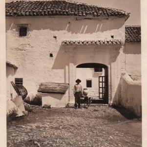 """Una de las puertas de acceso al cortijo donde un trabajador posa con un mastín (1932). Foto cedida por Manuel Guerra. Más información en """"Setenil Rural"""" http://goo.gl/PG35uX"""