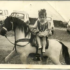 """EL SEAT 600. En esta imagen vemos a Ana Carmen Andrades posando para el fotógrafo en romería en un caballo de cartón en 1969 o 1970. Detrás podemos ver el parque automovilístico de aquellos años: tres seítas y Renault """"Cuatro latas"""". El Seat 600 fue mucho más que el primer coche de muchas familias, fue el símbolo de la época desde que comenzara a fabricarse en 1957."""