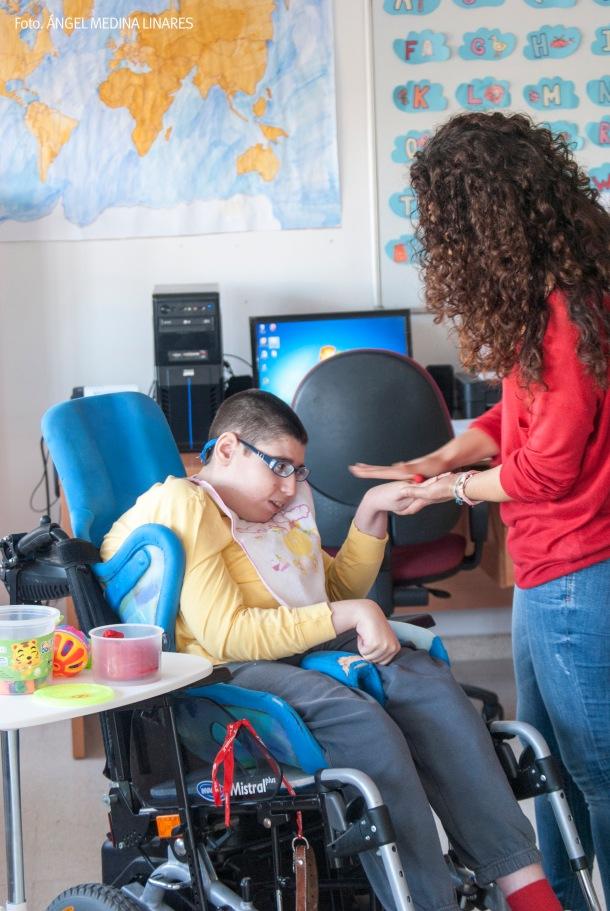 Miguel responde a los estímulos fisicos de Paqui Aguilera, la pedagoga de Sonrisa Libre. A Miguel le encantan los juegos, que mejoran su motricidad. Foto: ÁNGEL MEDINA LINARES