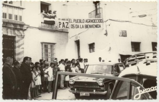 """Recepción en la Plaza a la comitiva del Gobernador Civil, Santiago Guillén Moreno, con pancartas alusivas a la campaña """"25 años de paz"""" ideada por el entonces ministro Manuel Fraga. Foto: JUMAN"""