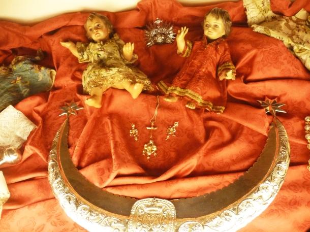 Media Luna de Plata datada en el siglo S. XVIII, y que procesiona delante de Nuestra Virgen de los Dolores. Detrás, esculturas del Niño Jesús originales del S. XVIII y vestidos de seda de la misma fecha. Foto JACKY KOOKER REAL