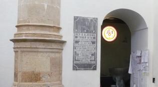 Una placa de márcol recuerda en la Iglesia d el Villa al sacerdote Luis Tovar Hita. Tras la restauración se ha desplazado al interior del baptisterio.