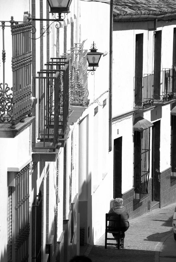 """Imagen de la calle Vega, con Catalina Cubiles sentada al solecito. Nos dice el autor: """"Me encanta colaborar con ese lindo lugar tan cercano y no muy conocido, casi tan malagueño como gaditano con una gente amable dispuesta a ayudar al visitante"""". Foto. CURRO VÁZQUEZ. Más imágenes suyas en http://bit.ly/1Em6vzP"""