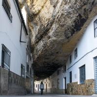 Esta fotografía tiene un misterio especial. Pocas veces se ha retratado tan bien el impacto de la roca y la insignificancia humana bajo su peso, en esa calle sin paragón y a veces sin coches, en la que parece escucharse el silencio de la mañana antes del aluvión turístico. Foto: ACALU ESTUDIO. Más imágenes en su web http://acalu.es/#inicio