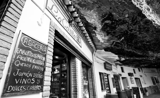 No, esta imagen no es un montaje. Es la realidad: un calle cubierta por la roca que sostiene una carretera, en la que viven los vecinos y donde se pueden comprar y consumir productos made in Setenil. Un lujo de sitio, bien surtido de comercio y bares. Foto: CARMELO TORRENTE. https://flic.kr/p/qoQU23