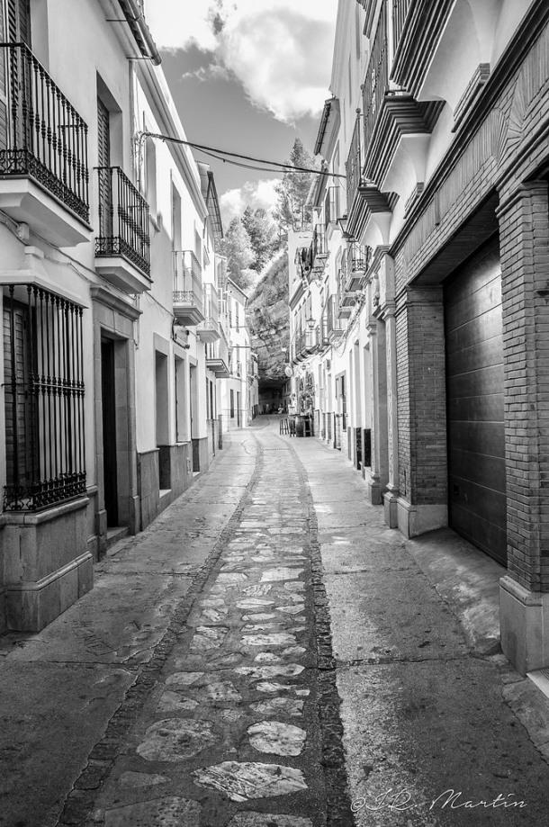 La calle Ronda, con Las Cuevas de la Sombra al fondo y, en un nivel superior, la carretera que nos lleva a la Ventosilla y San Sebastián. Foto: JUAN R. MARTIN. https://flic.kr/p/pfqaqE