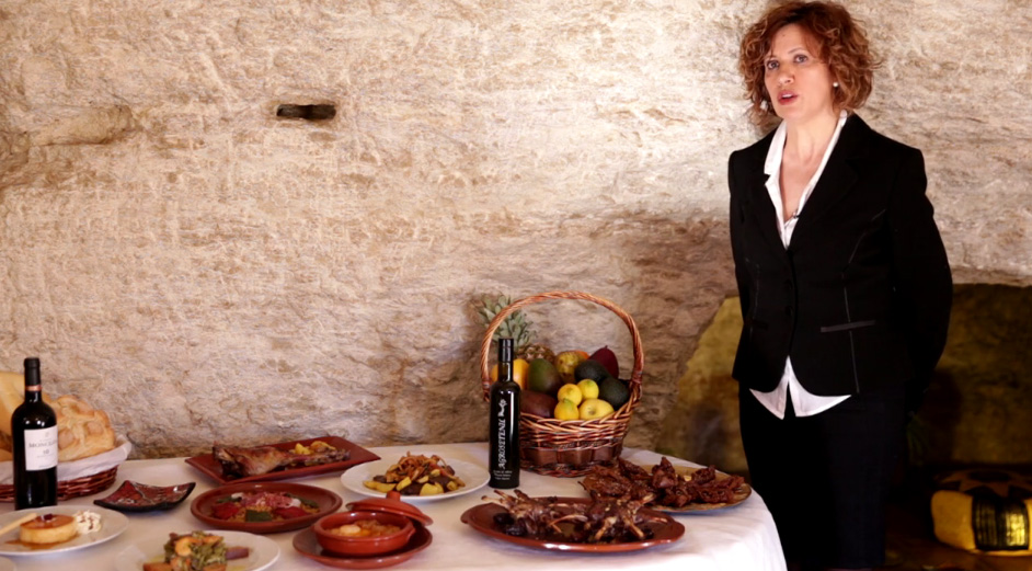Inmaculada Robles muestra las migas que hacen en el restaurante Palmero, con el fondo de roca, en los mismos cimientos del Torreón.