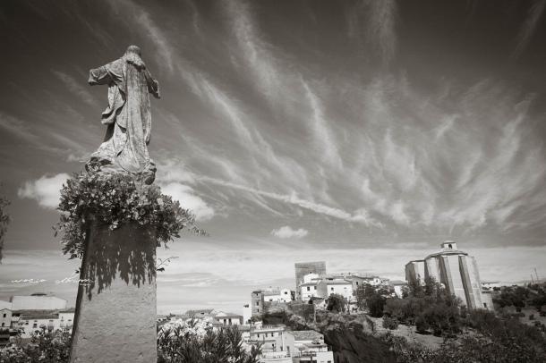 Perspectiva de la fortaleza medieval de Setenil desde El Carmen, con la dañada estatua del Cristo en primer término. Foto: ROCÍO ALHAMA. https://flic.kr/p/fjZ3b3