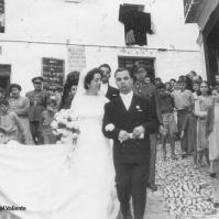 """LAS BODAS. Entrañable imagen de la boda de Paca Guzmán, en los años cincuenta. Escoltada por los tres municipales, con la ropa interior colgada de los balcones de la calle principal del pueblo, con la programación del cine al fondo y el bullicio en la antigua plaza de abastos (donde ahora está el supermercado de Conchi). La imagen se publicó en el grupo de Facebook """"Setenil y los setenileños es lo que importa""""."""