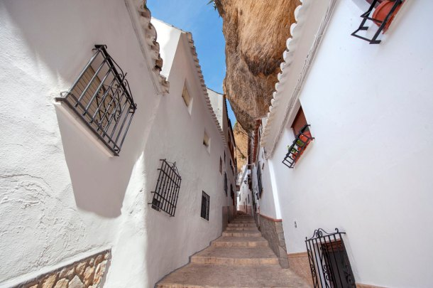 """La calle Herrería, una de las más antiguas y emblemáticas calle-cueva de Setenil, en los cimientos mismos de la fortaleza medieval. """"Hola"""" ilustra su reportaje con esta luminosa fotografía del PATRONATO DE TURISMO DE CÁDIZ."""
