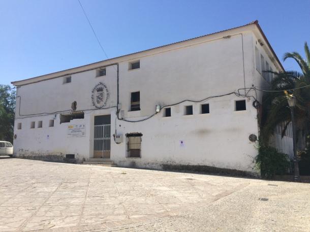 El antiguo colegio, fotografiado desde la ermita del Carmen, a la que supera con creces en envergadura. Es un auténtico muro para El Carmen, que priva a sus vecinos y a los visitantes de unas privilegiadas vistas hacia el río y el admirado caserío de Setenil