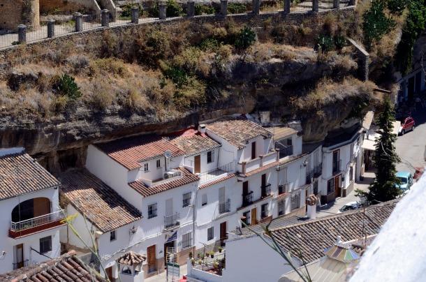 """Las Cuevas del Sol reúne tanto viviendas """"adosadas"""" (que vemos en primer término) como """"al abrigo de roca"""", que se aprecia en cualquiera de los bares y comercios de esta calle. Foto: JOSÉ CARLOS MESA."""