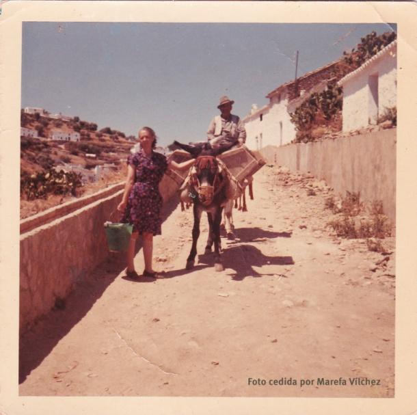 Marisabel Guzmán Gutiérrez y su tío Rafael Gutiérrez Domínguez, que vivía en El Carril, el padre de Maribel. La fecha aproximada es 1965, o quizá un poco antes. Según nos cuenta Marefa Vílchez, que nos ha cedido la foto, Rafael Gutiérrez se dedicaba a coger arena para las obras, que trasladaba en este mulo. Marisabel vendría posiblemente de coger agua y lavar en el río. Esta fotografía nos muestra la enorme transformación que ha experimentado el Cerrillo. Foto cedida por MAREFA VÍLCHEZ.