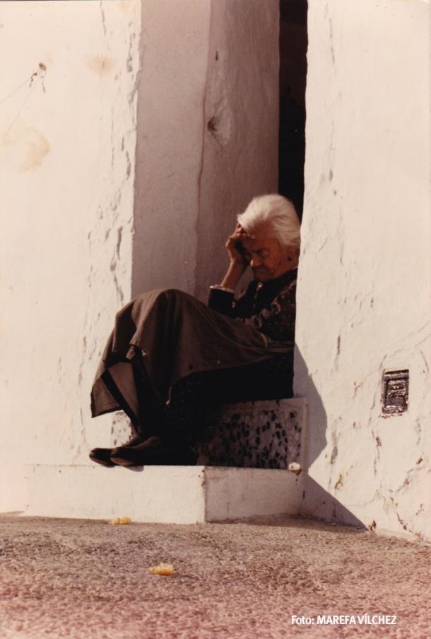 En el umbral. Marefa Vílchez consiguió estahermosa postal del paisanaje de nuestro pueblo a finales de los ochenta. Fotografíó a Ana la de Juan Cabeza, sentada en la puerta de su casa del Cerrillo, en un momento de duermevela quees pura emoción y belleza.