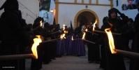 Los hermanos, portando antorchas, arropan la Cruz de Padre Jesús. Llevan antifaz, pero sin capirote. Aquí les vemos saliendo de la ermita de San Benito. FOTO: ÁNGEL MEDINA LAÍN