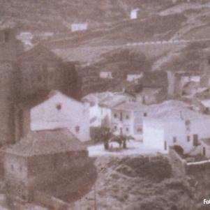 Esta imagen, de finales de los años 50, es un detalle de una foto realizada por JUAN MARÍN ORTEGA. Aquí se aprecia la fachada blanca de la parroquia, el antiguo Seminario a sus pies y la caída natural de la peña hacia Los Cortinales, abortada con la desafortunada urbanización de la plaza.
