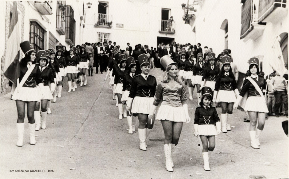 """Las 'majorettes' en Setenil. En Setenil fue muy popular la """"guerra de bandas"""" en las últimas décadas del siglo pasado. En pleno desenfreno por conseguir la agrupación más vistosa y llamativa llegó hasta el pueblo en 1969 la norteamericana """"Banda de Majorettes Shawthorne Sombreros"""", que actuaba ese año en Málaga. Cuenta Pedro Luis Marín en su libro """"Un siglo en Blanco y Negro"""" (2002) que esta agrupación femenina fue contratada por Los Negros por 200.000 pesetas de la época para hacer un pasacalle y que no procesionó. Una llovizna deslució el desfile de estas jóvenes animadoras en minifalda. """"Fue tanta la conmoción que causó que varios de nuestros paisanos quisieron irse con la agrupación a los Estados Unidos"""", relata. Algún año después, Los Blancos se sumaron a la apuesta con un pasacalles de estas populares animadoras en Domingo de Resurrección. Foto cedida por MANUEL GUERRA."""