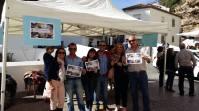 El alcalde posa en el stand de la campaña de apoyo a la candidatura de Setenil. Foto: Ayuntamiento de Setenil.