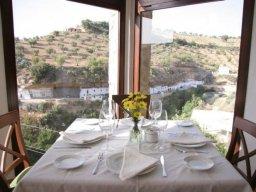 Una de las mesas del restaurante El Mirador, con vistas a la clle-cueva Cabrerizas.