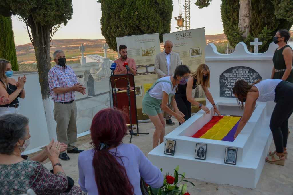 Miembros de la Asociación de la Memoria Histórica de Setenil colocan una bandera republicana en la tumba que acoge los restos de los fusilados.