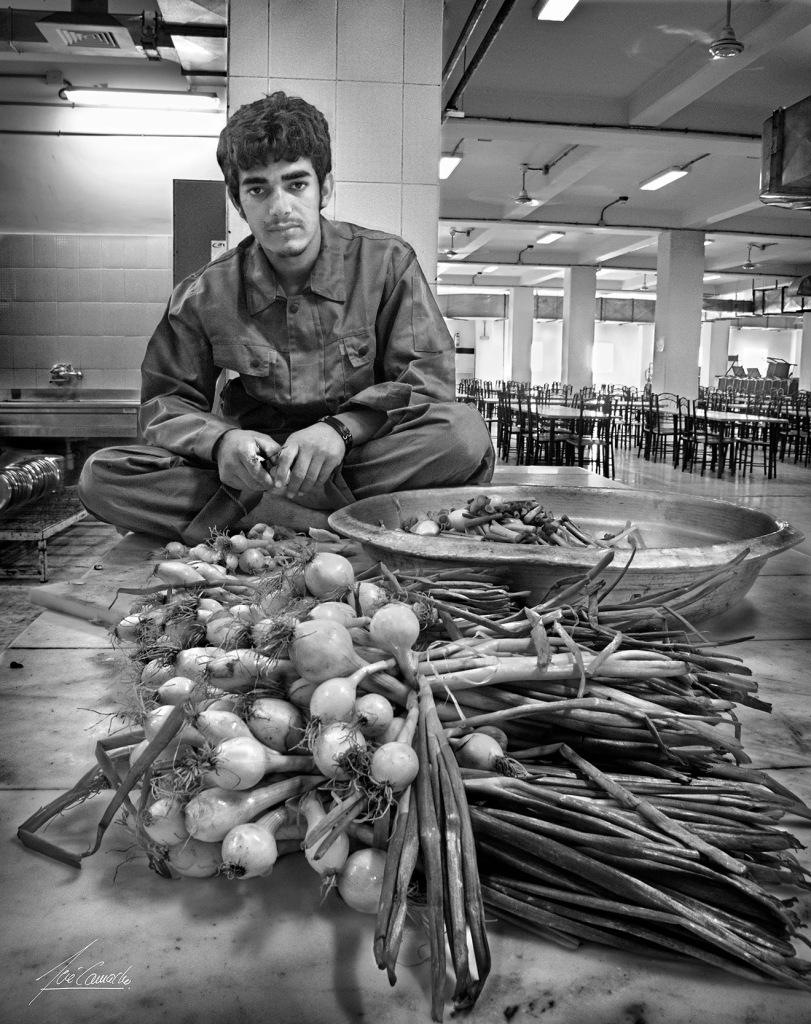 """""""Joven con cebollas. Pinche de la cocina de Camp Zafar encargado de pelar cebollas. Me llamó la atención su juventud (normalmente el personal de la cocina era bastante mayor), la posición que adoptó para hacer su trabajo y sobre todo su triste mirada""""."""