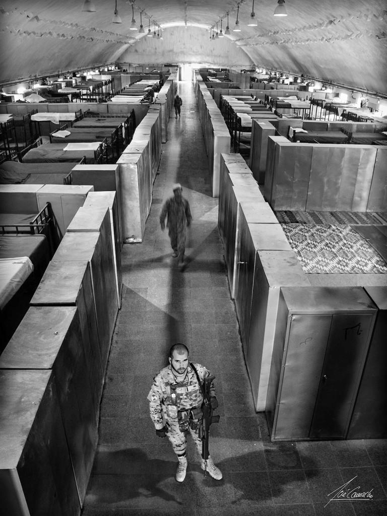 """""""Interiores. Interior del dormitorio del Kandak. En primer plano un soldado español, que por motivos de seguridad custodia la entrada. Este edificio, además de las oficinas de las Compañías, era el dormitorio de algunos Oficiales y Suboficiales y por supuesto el de la tropa, llegando a albergar unos 400 hombres""""."""